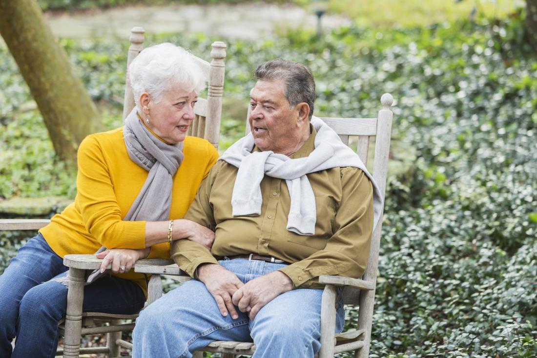 Ältere Paare, die auf Holzstühlen im Garten hat Gespräch sitzen.