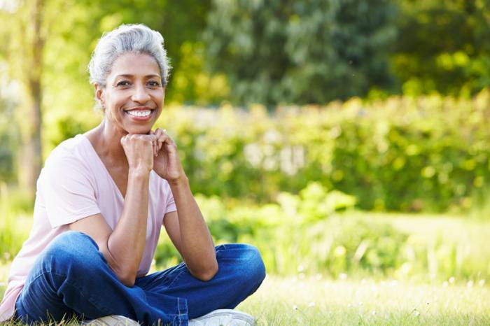 Một phụ nữ lớn tuổi ngồi bên ngoài.