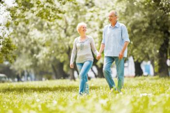 Một cặp vợ chồng già đi bộ trong công viên.