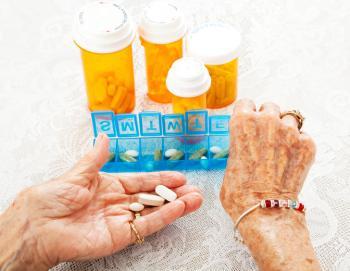 [Una donna anziana che organizza le sue medicine]