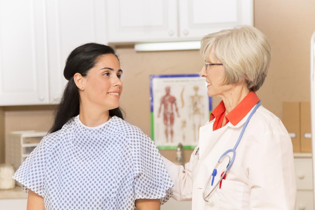 Người phụ nữ trong áo choàng bệnh viện nghe bác sĩ.
