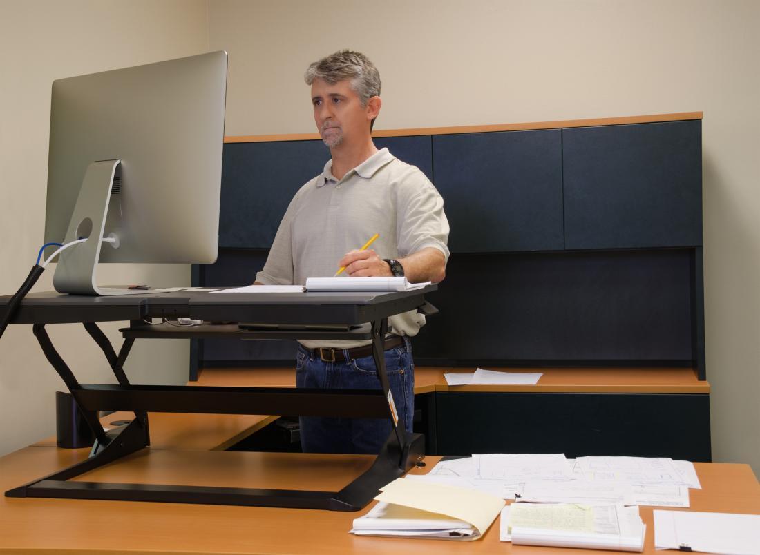 立っている机を使っている男