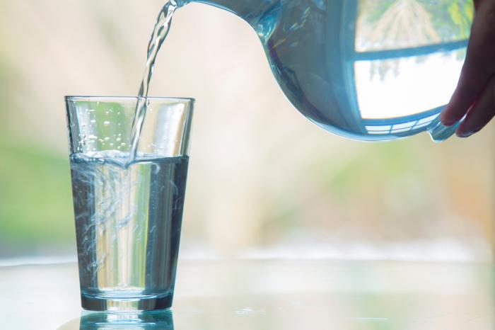 [Una persona che versa un bicchiere d'acqua]