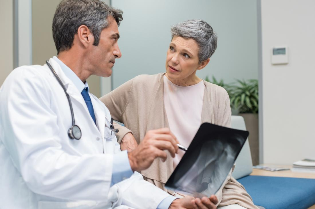 Doktor, der Röntgenstrahl älteren Patienten erklärt
