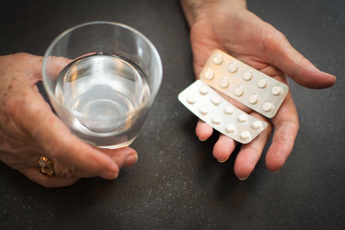 възрастните ръце, държащи таблетки и вода