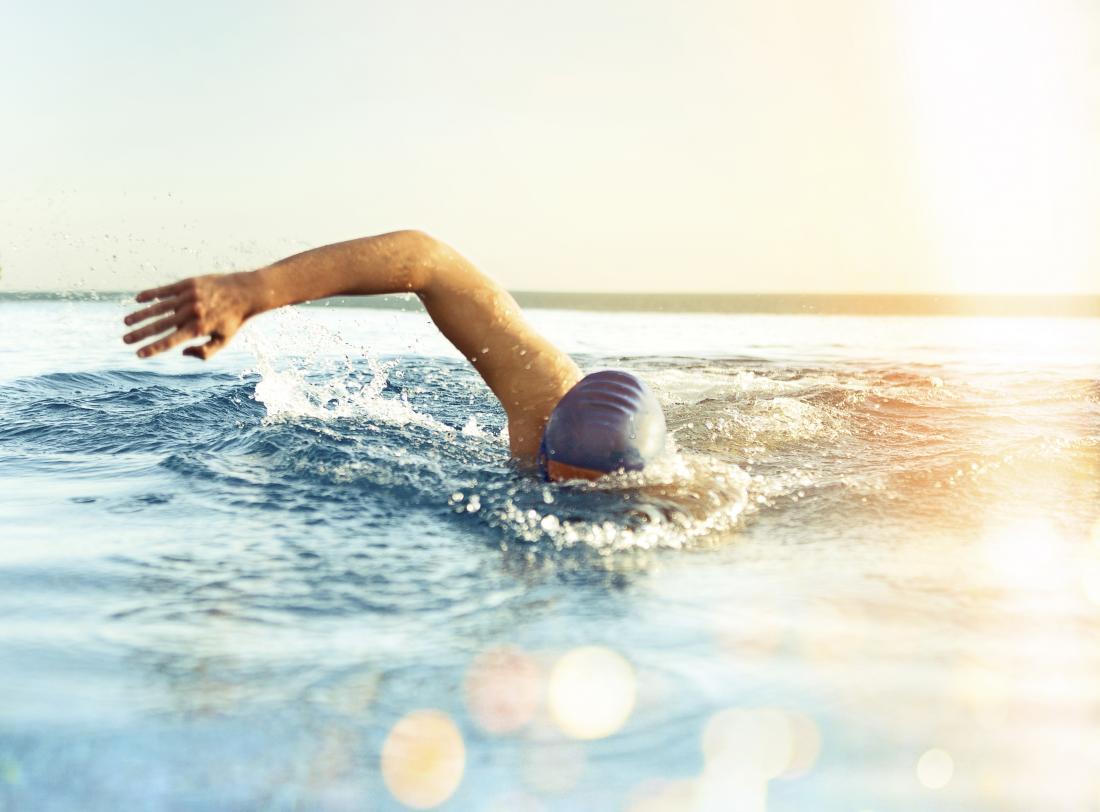 човек плува в басейн