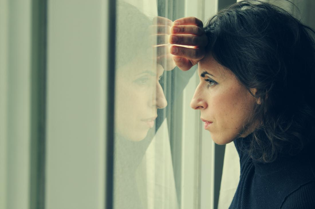 Sombre người phụ nữ nhìn ra ngoài cửa sổ.