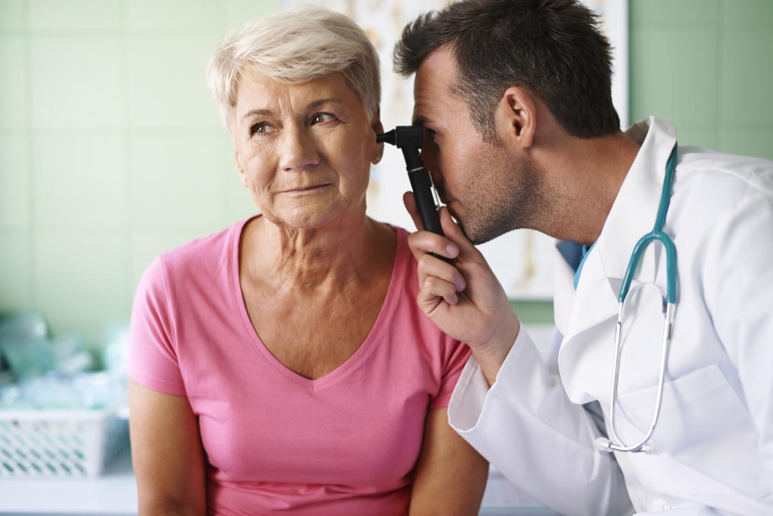 Femme âgée ayant l'oreille inspectée par le médecin.