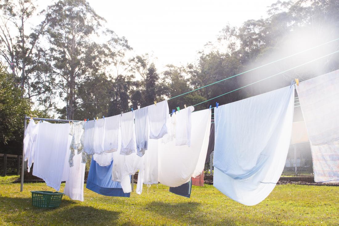 Kleidung, die draußen auf Wäscheleine im Garten trocknet.