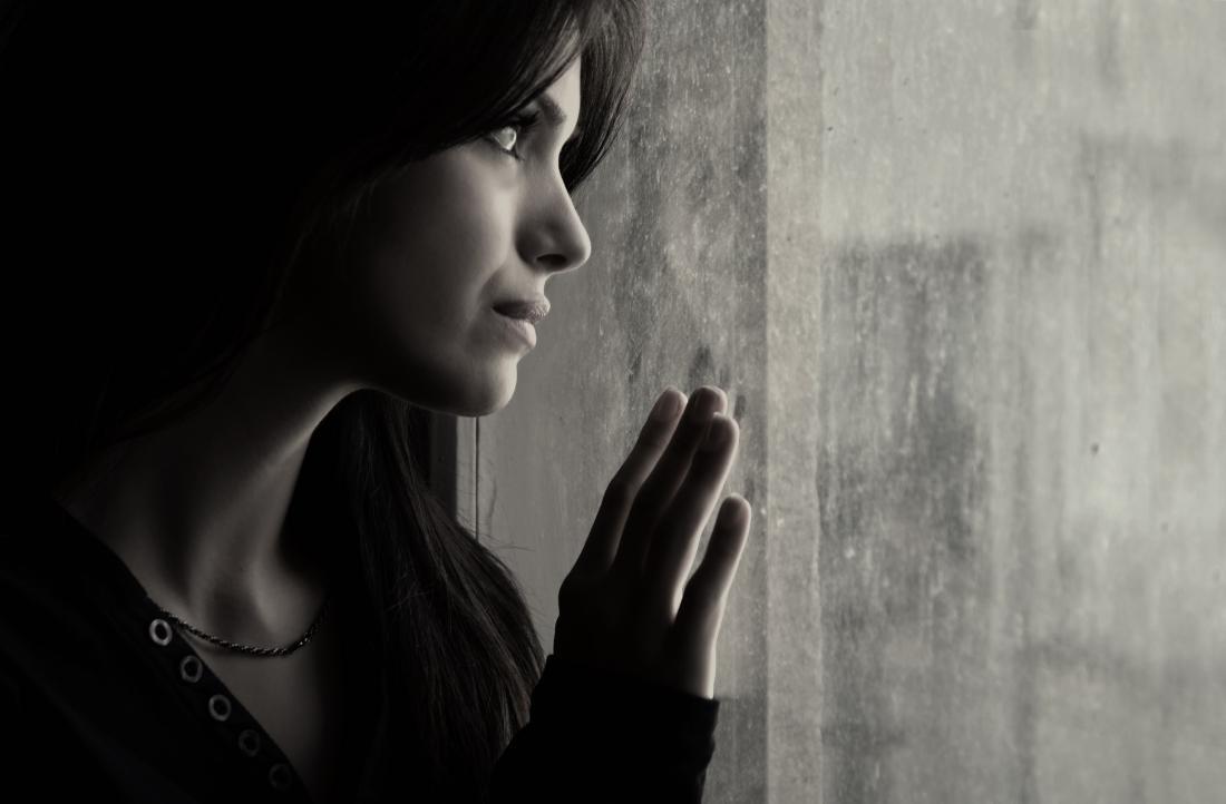 una donna triste che guarda fuori dalla finestra