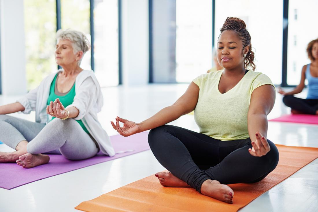 [Frauen machen Yoga in einem hellen Raum]