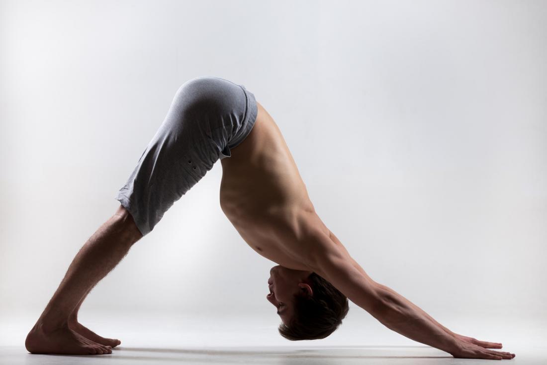[junger Mann macht nach unten gerichteten Hund Yoga-Pose]