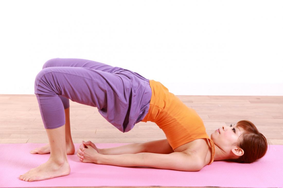[junge Frau macht Brückenpose Yoga]