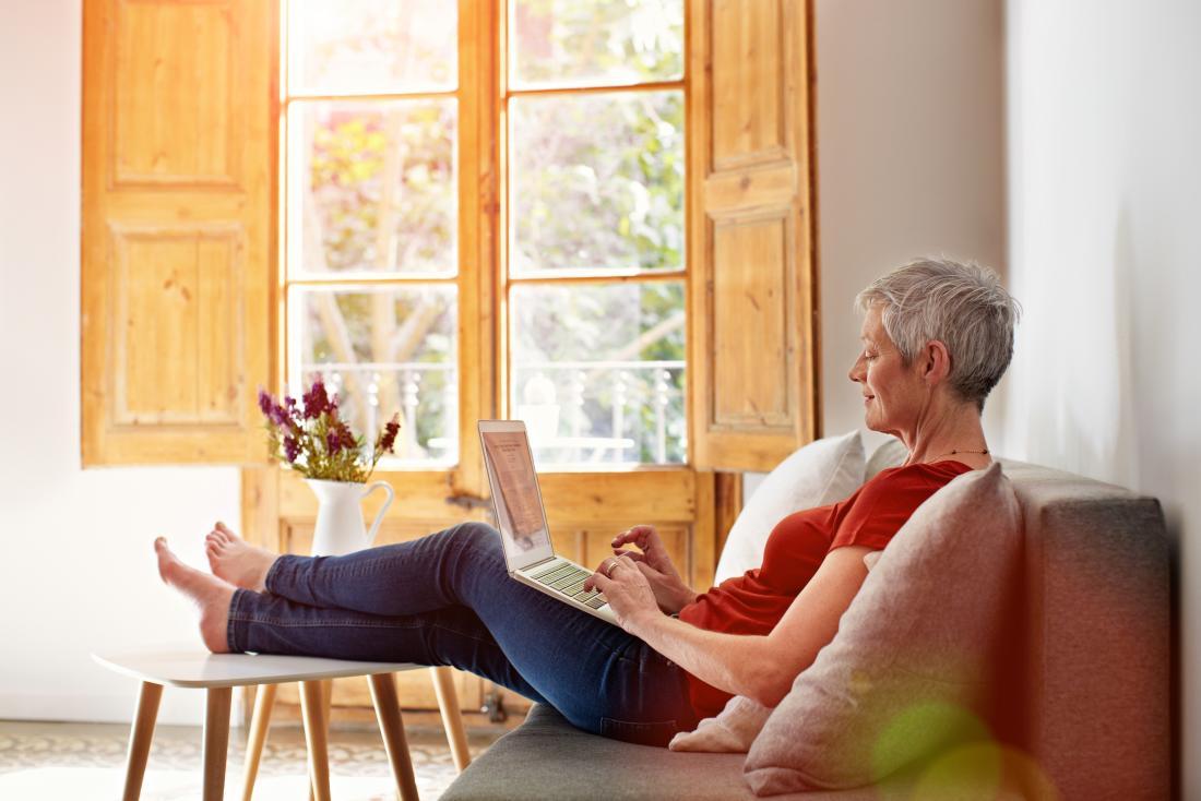 年配の女性がノートパソコンに座っている