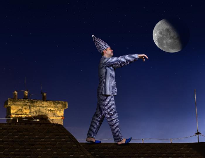 Schlafwandelnder Mann auf einem Dach.