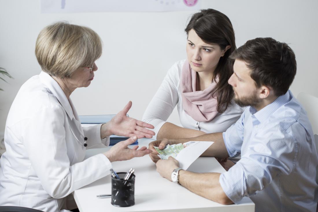 Couple discutant de traitement de la fertilité avec un médecin.