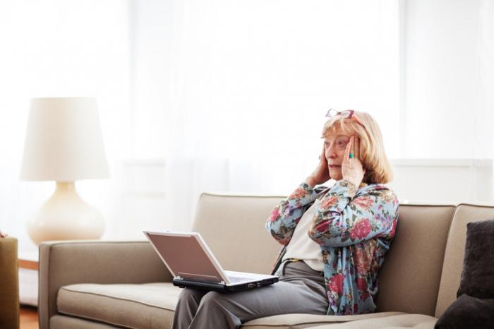 老婦人は混乱してラップトップでラップを心配している
