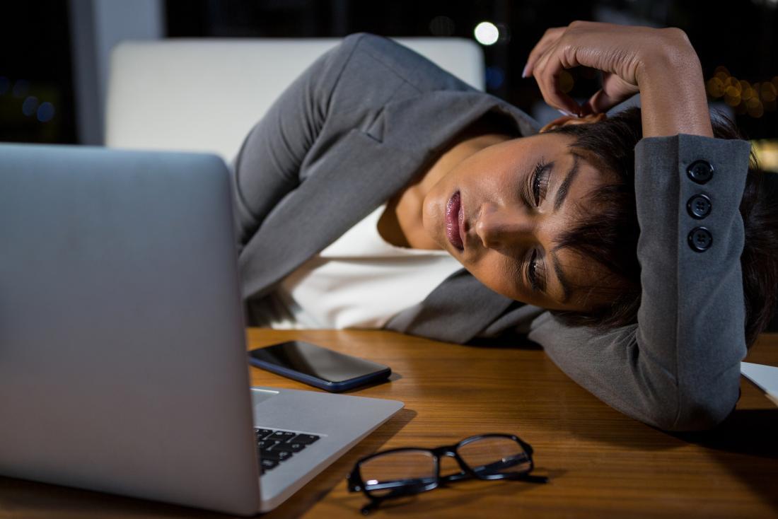 una donna che si addormenta alla sua scrivania