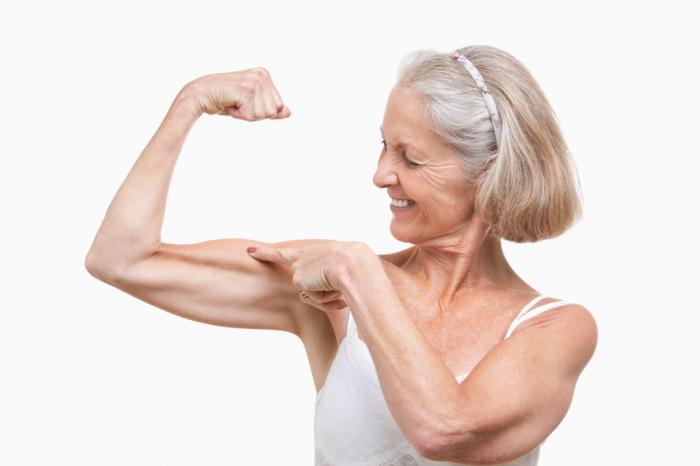 [Mulher idosa mostrando seus músculos]