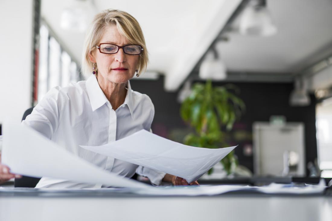 仕事で紙をジャグリングする年上の女性