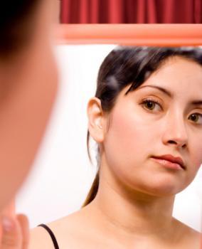 [Una donna che si guarda allo specchio]