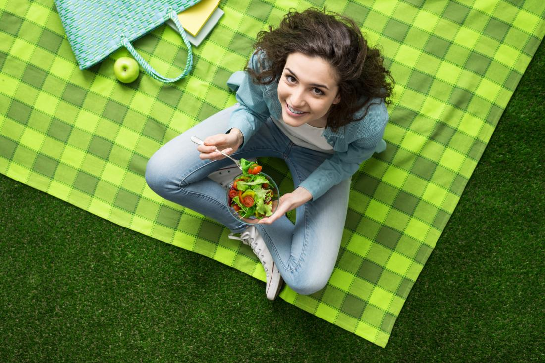 mulher sentada em um cobertor de piquenique
