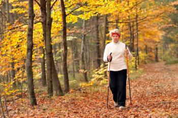 femme plus âgée avec des bâtons marchant dans les bois feuillus