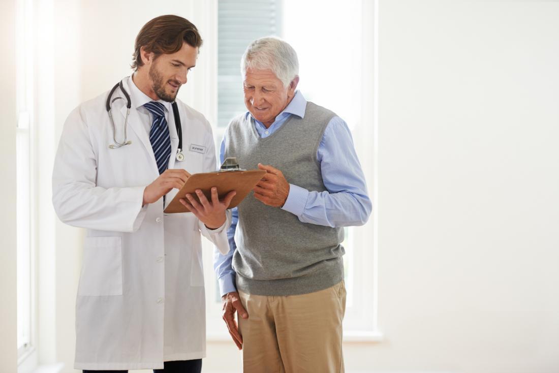 Paciente sênior que fala com um doutor masculino, olhando uma prancheta.