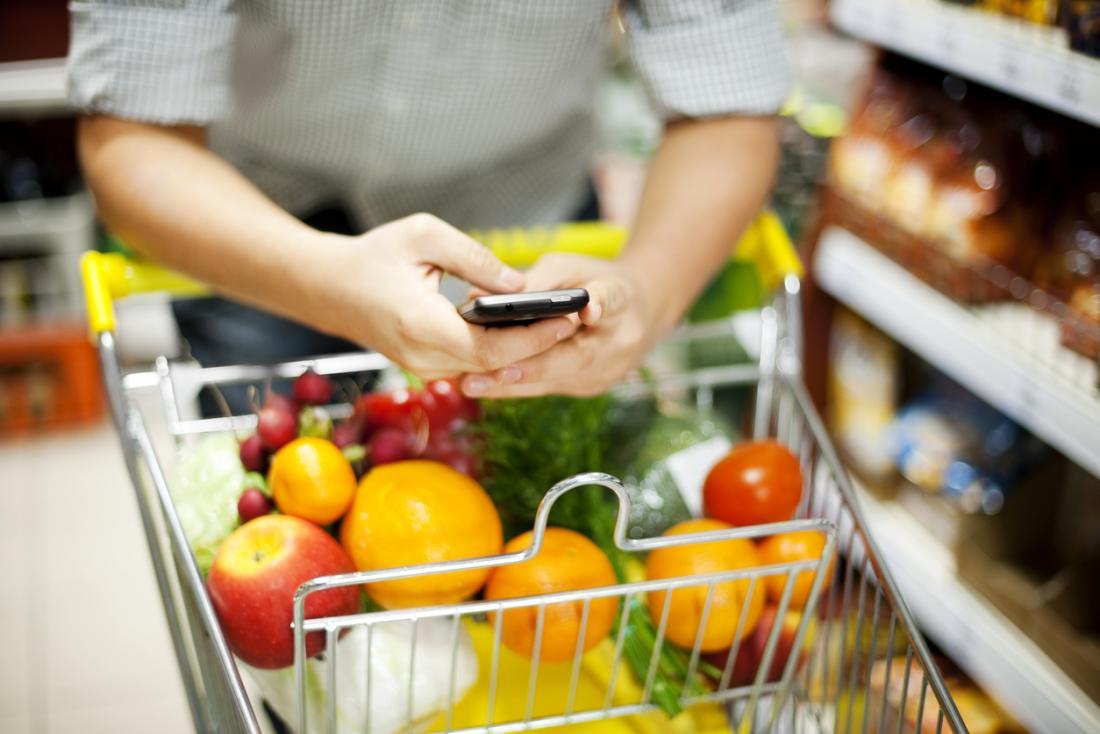 homem no telefone inteligente no supermercado