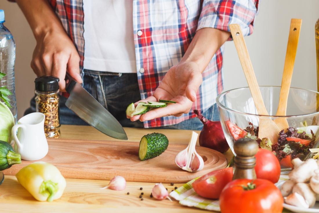 pessoa cortar pepino para fazer salada