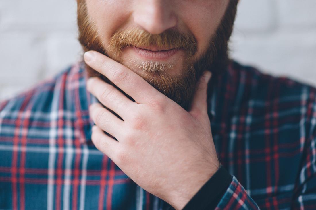 Mann mit dem juckenden Bart, der sein Kinn berührt.