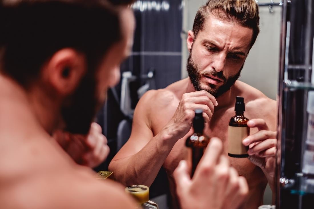 Ein Mann mit trockener Haut und einem juckenden Bart vor dem Badezimmerspiegel, der Gesichtsölflasche betrachtet.