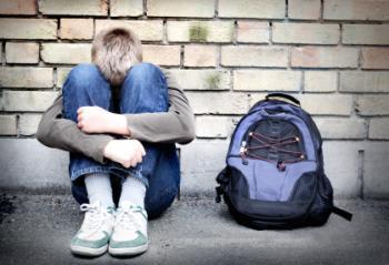 彼の膝を抱きしめる十代の若者