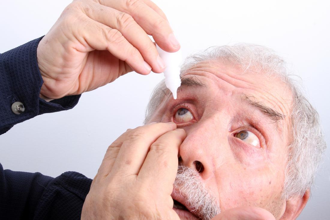 homme senior, appliquer des gouttes pour les yeux à cause des yeux qui brûlent