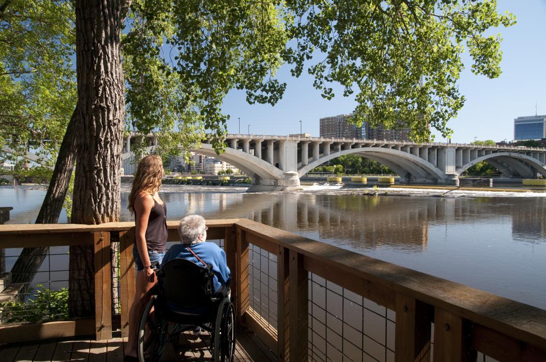 Person im Rollstuhl und Begleiter genießen Aussicht