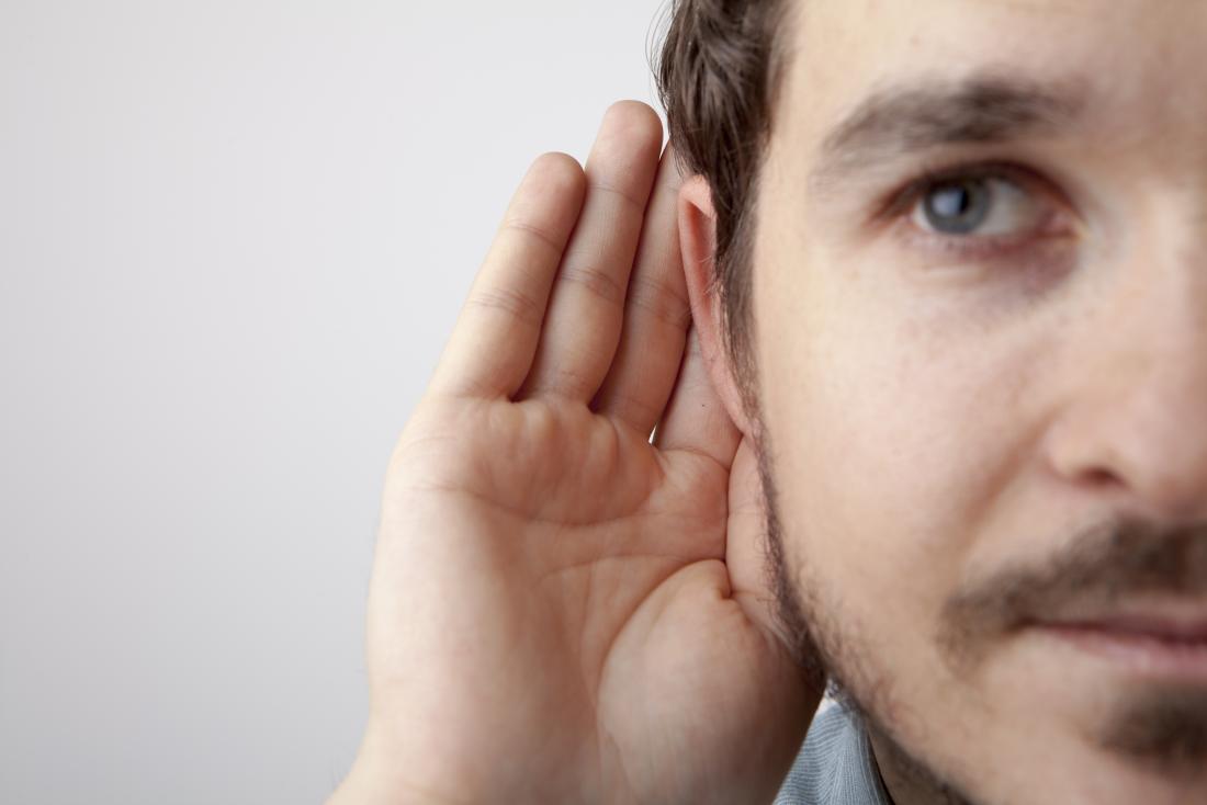 Homem colocando a mão no ouvido devido a infecção do ouvido duplo