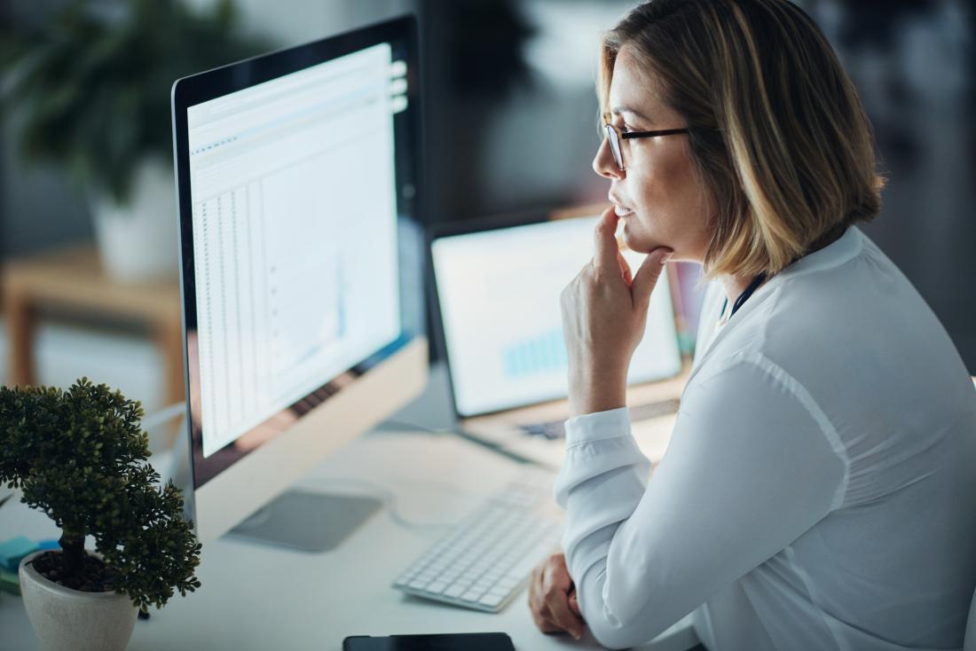 femme regardant les écrans d'ordinateur au travail.