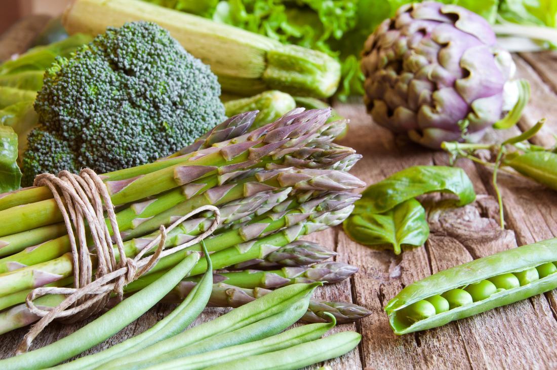 Divers légumes verts, y compris le brocoli, les pois, les haricots verts, l'artichaut, la salade, la courge et la moelle.