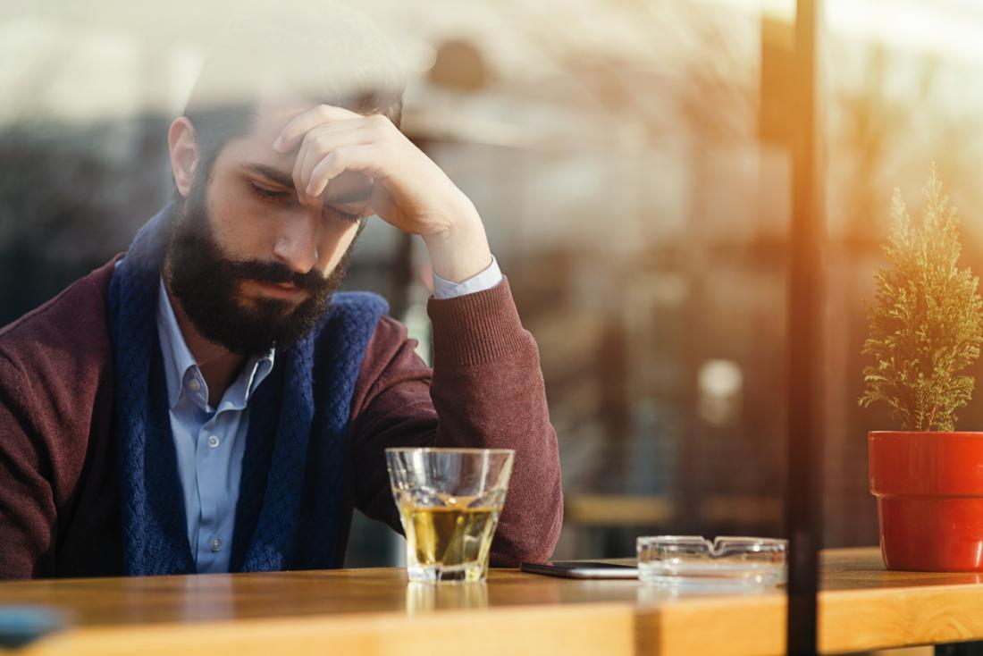 Uomo seduto di fronte a un bicchiere di alcol, cercando stressato e depresso.