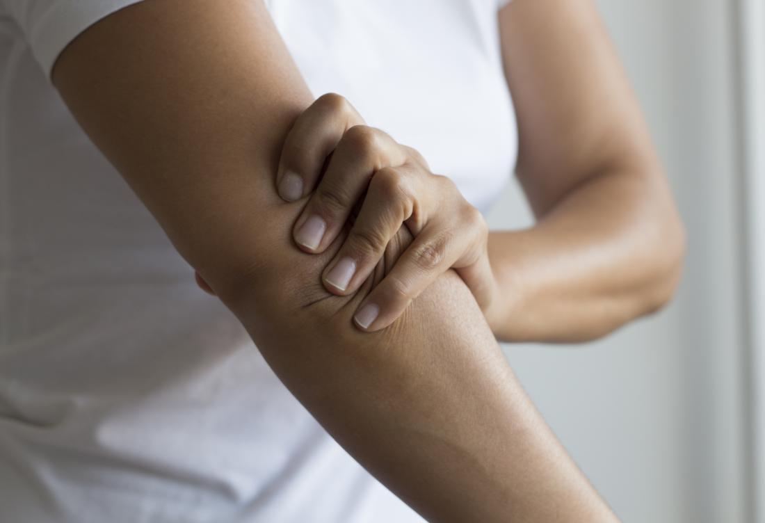 Articulações rígidas no cotovelo seguradas pela mulher.