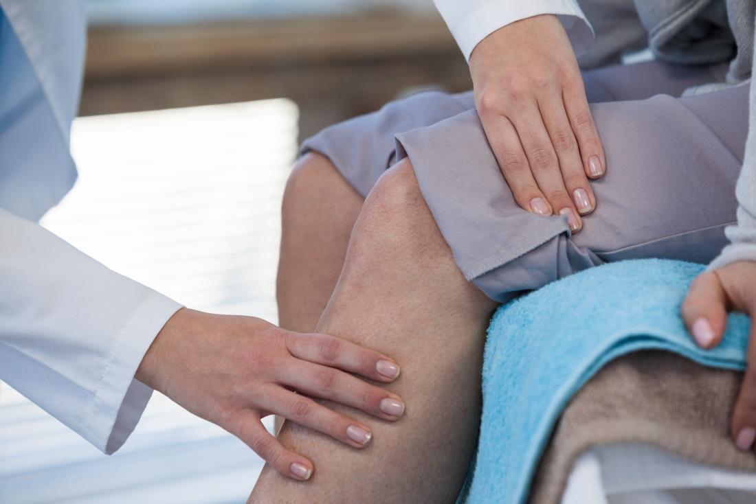 Doutor que inspeciona o joelho dos pacientes para a dor articular como se sentam na cama.