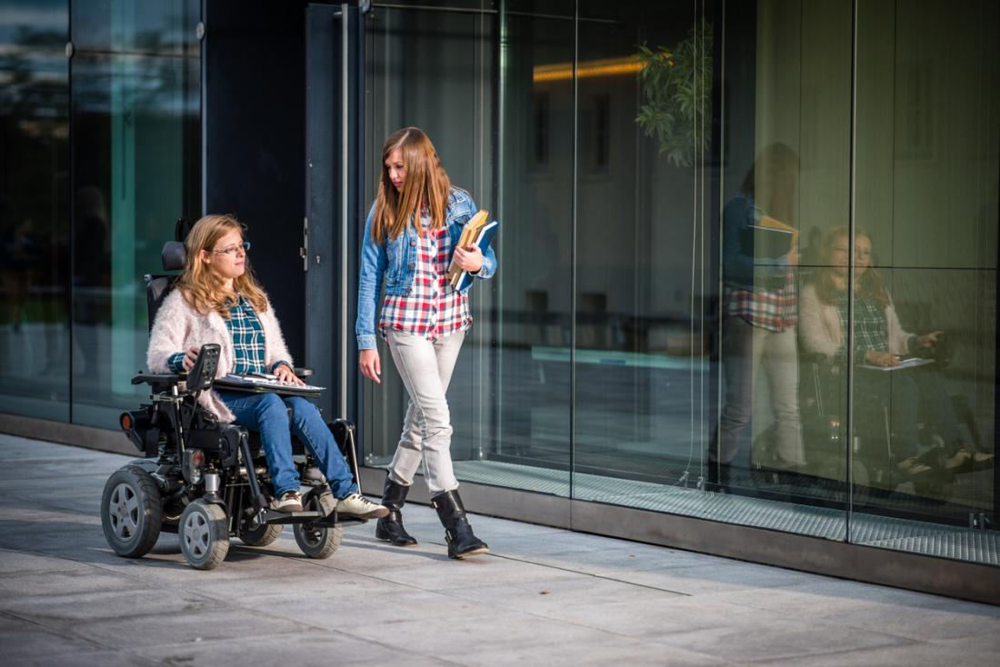 Junge Frau mit multipler Sklerose im Rollstuhl neben junger Frau auf dem Campus.