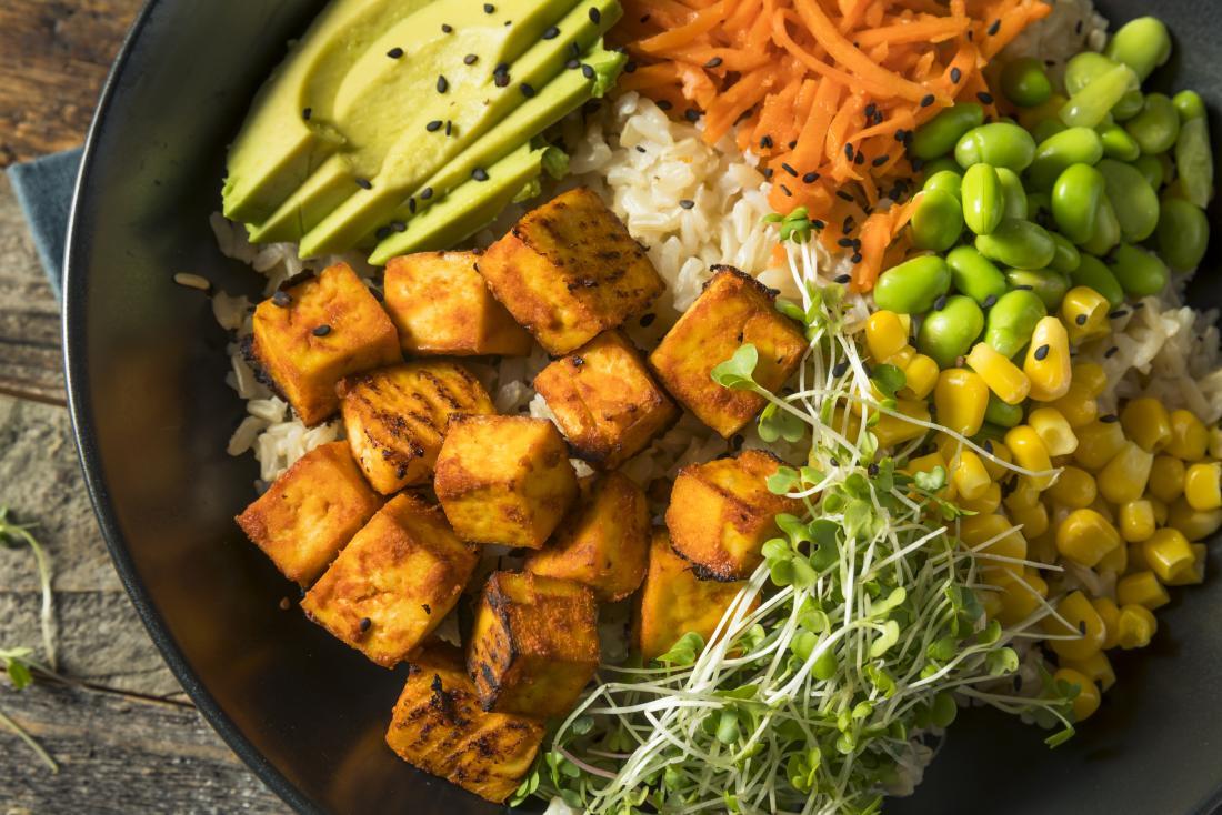Gesunde und nahrhafte pflanzliche Mahlzeit für die Hepatitis-C-Diät, einschließlich Tofu, brauner Reis, Bohnen, Avocado, Karotte, Brunnenkresse und Mais.