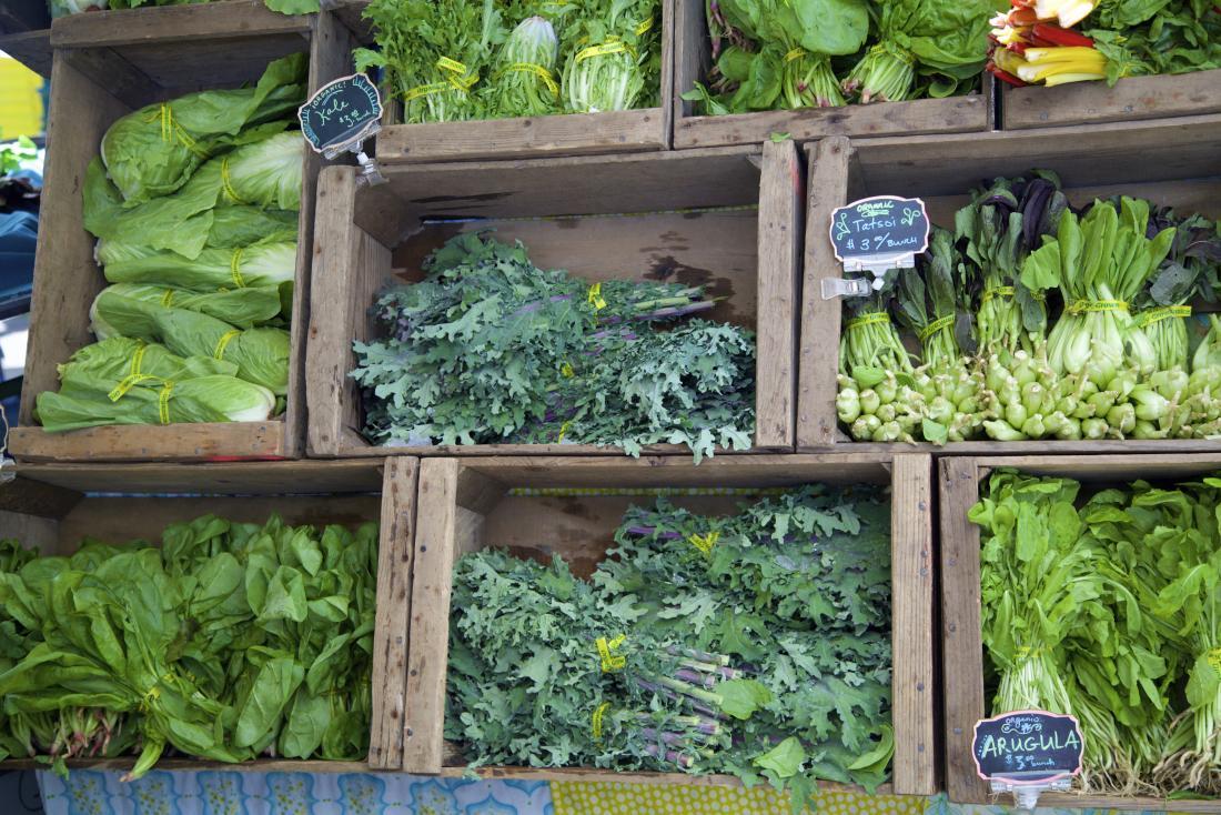 Dunkelgrünes Blattgemüse im Markt, einschließlich Kohl, Kohl und Spinat.