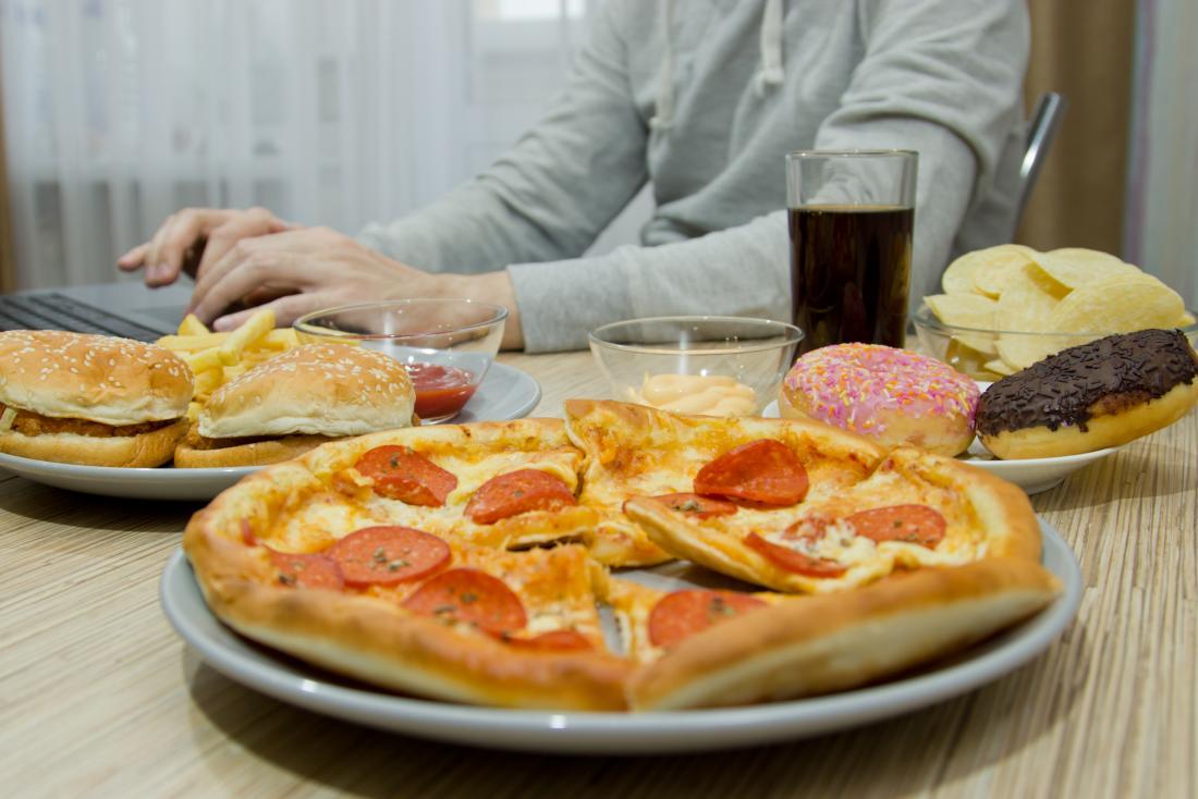 Person, die am Schreibtisch umgeben durch ungesundes, hohes Fett, Salz und addierte Zuckernahrungsmittel einschließlich Cola, Pizza, Schaumgummiringe, Chips, Burger, Chips und Ketschup arbeitet.