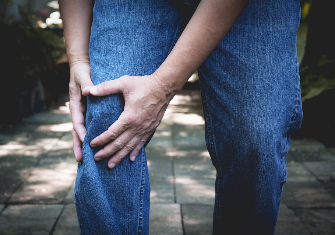 Homem segurando o joelho devido a osteoartrite tricompartimental