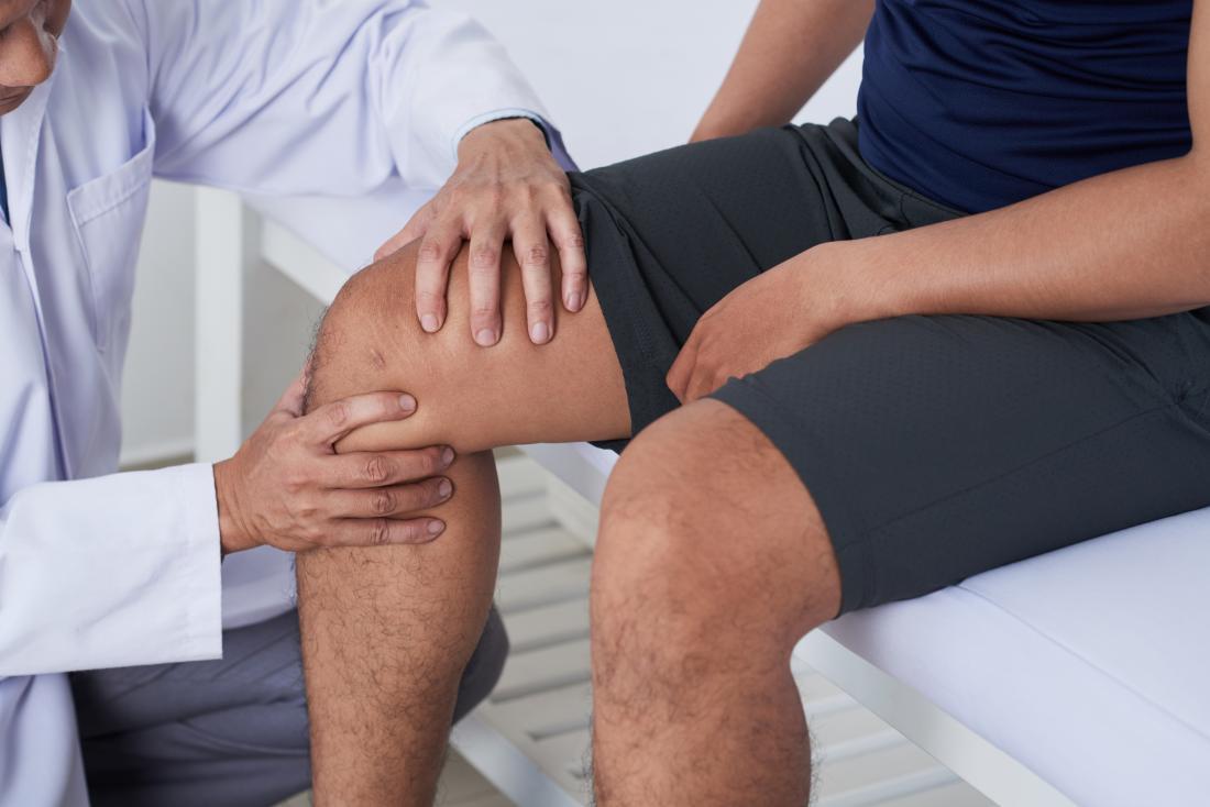 Doutor examinando o joelho para diagnosticar osteoartrite tricompartimental