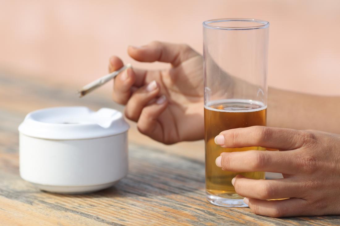 personne ayant une boisson et une fumée