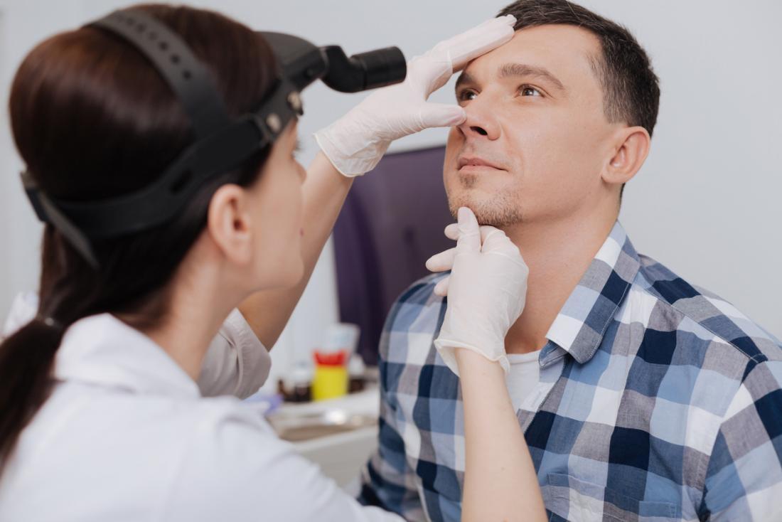 女性の医者はくすぐりの原因のために人間の鼻を検査する。